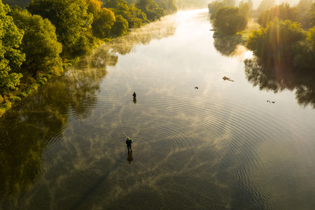 aerial shot of a man fly fishing in a river during summer morning