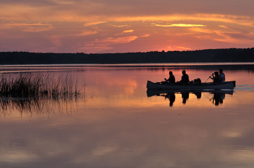 Group rowing in canoe at sunset